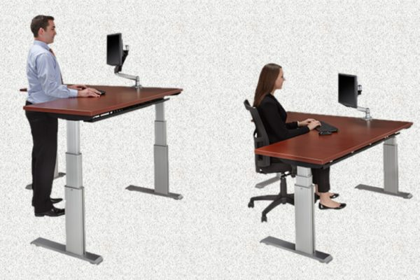 48x72 extended corner 3-stage electric sit-stand desk with programmable height settings, silver powdercoat legs, and medium cherry laminate.
