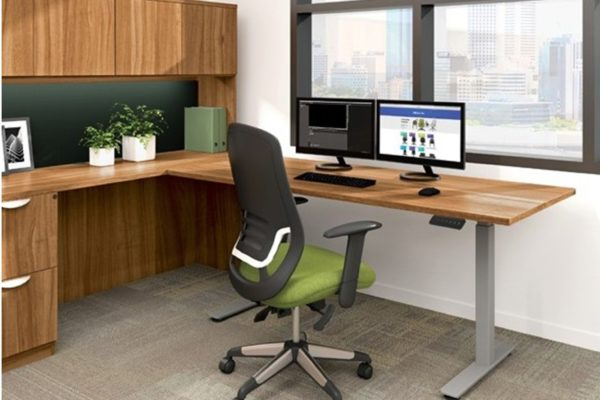 30x60 integrated sit-stand return desk with natural cherry laminate, gray legs, and dual monitor setup.