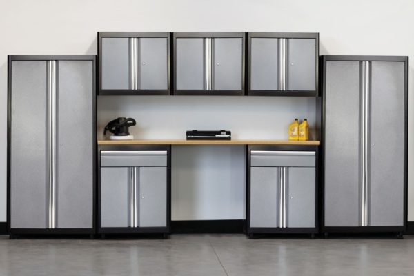 Light-industrial storage cabinets with graphite powdercoat cases and ribbed stainless steel door accents, integrated with light-duty low height work bench finished with a butcher block top surface.