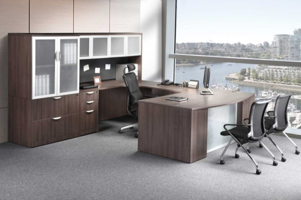 U-group in medium walnut laminate with glass accents, storage tower, and overhead hutch.