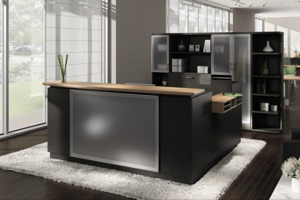 Espresso reception desk with return, glass front panel, aluminum-accented rear storage, paper management, and medium cherry accents.