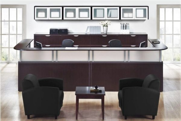 Double reception desk in espresso laminate with silver post transaction counters, rear lateral file storage bank, and wall hung overhead cabinets with aluminum framed doors.