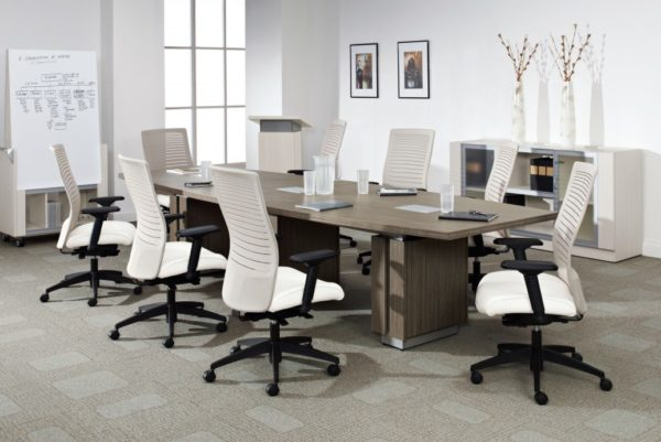 Executive 48x120 boat-shaped conference table with three built-in power modules, raised panel table bases with aluminum accents, and natural walnut laminate finish.