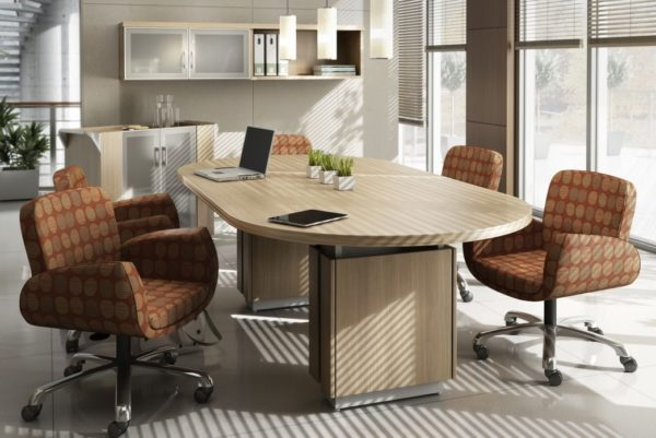 Executive 48x96 racetrack-shaped conference table with two raised panel bases and finished in natural walnut laminate with matching self edge.