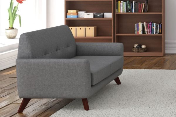 Angled loveseat in gray linen fabric with cherry angled wood legs. Buttoned detail on the seat back.