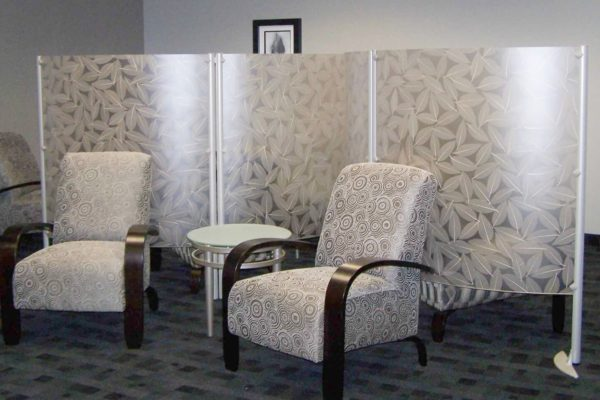 Lounge chairs with wide bent wood mahogany stained arms, designer fabric, accent table in white and tungsten, and acrylic privacy screens for safe distancing.