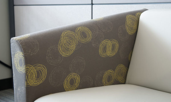 Arm detail of contemporary two-tone club chair in medium grey and cream-colored fabrics.