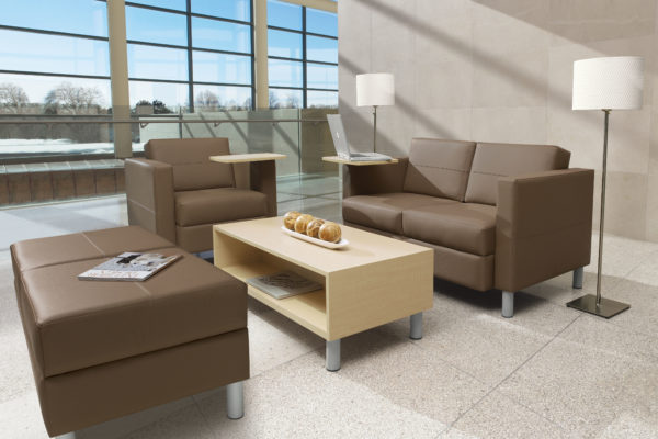Transitional waiting room furniture including loveseat and chair, integrated maple laminated writing tablets, matching brown leather ottoman, and matching maple coffee table with tungsten feet.