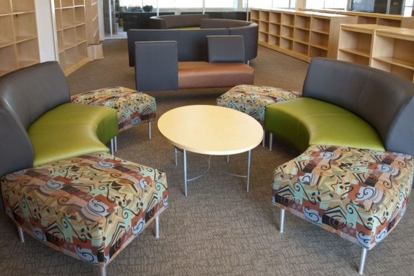 Circular waiting area ensemble with tungsten powdercoat legs, multi-color intermixed vinyls and fabrics, and matching oval-shaped coffee table.