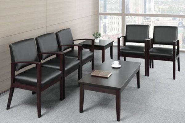 Wood-framed ganging waiting room chairs in black leather with mahogany frames including matching mahogany end table and coffee table.